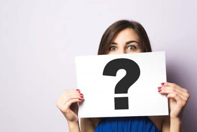 woman holding a question mark poster board in front of her guessing face