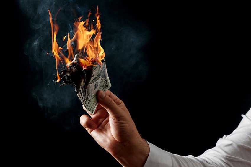 man holding money as it burns