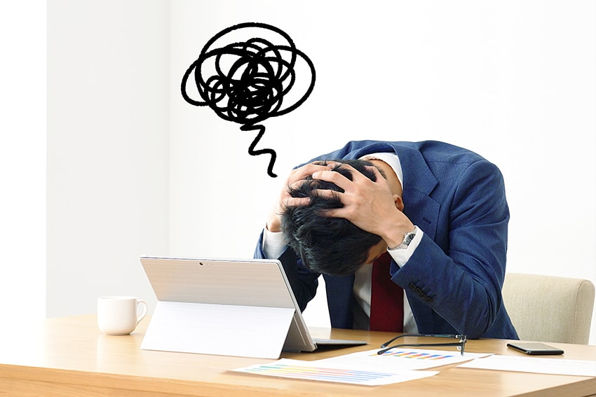 stressed out man holds his head down at his laptop